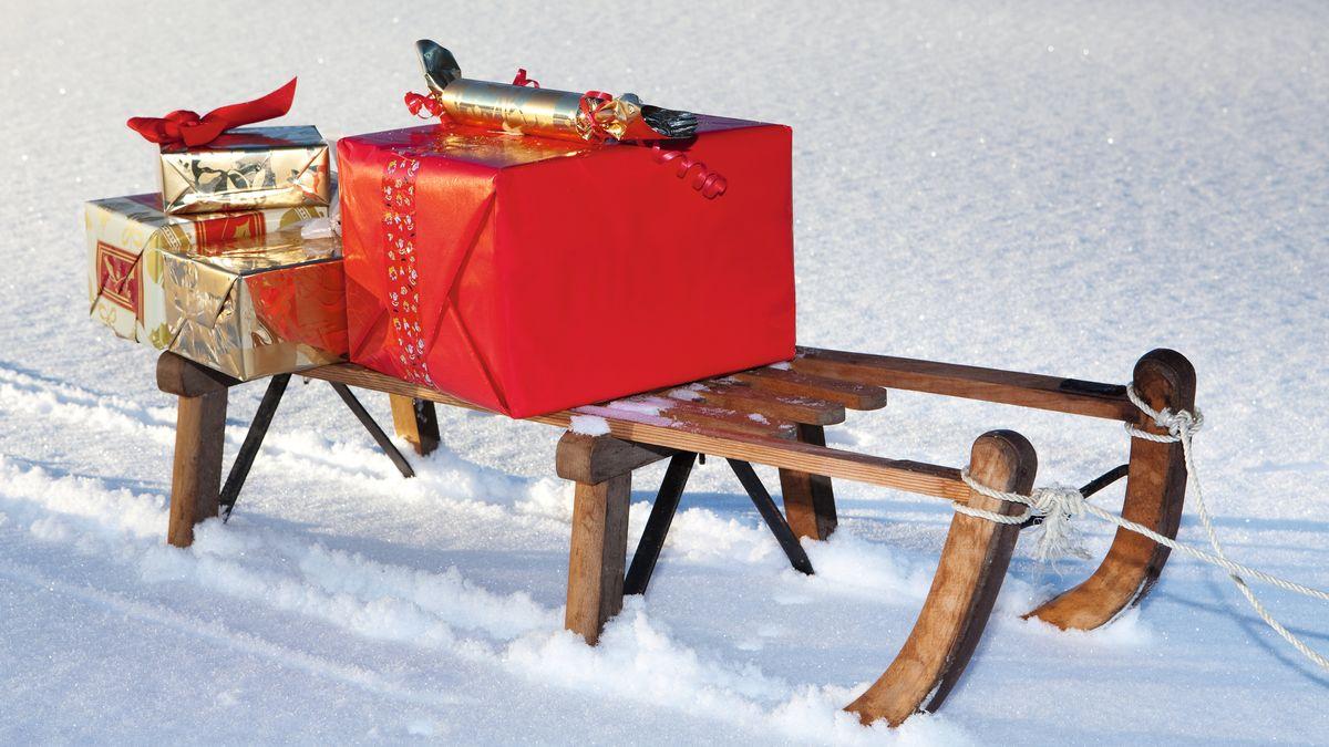 Weihnachtspäckchen liegen auf einem Schlitten im Schnee