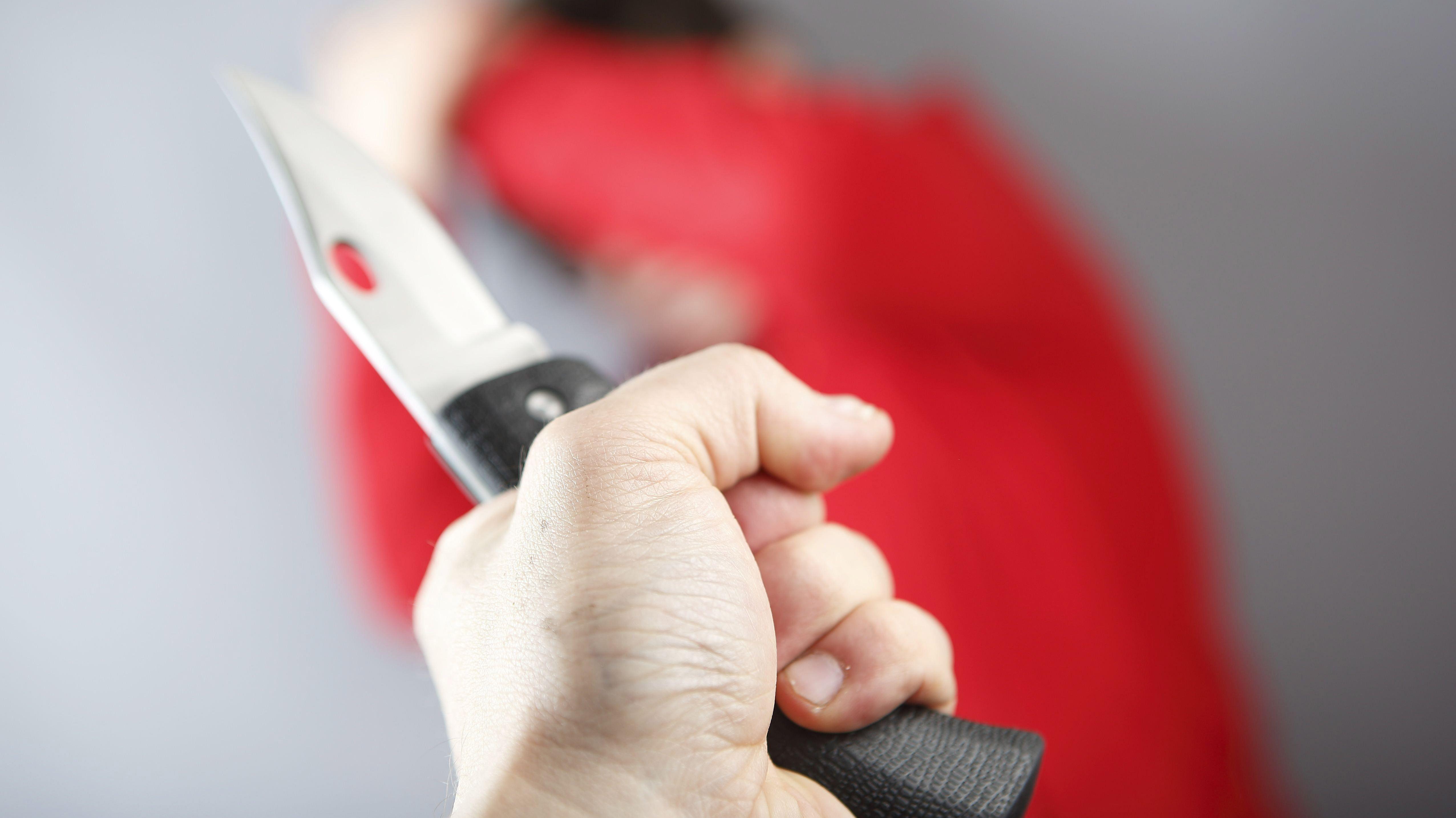 Mann hält Messer und bedroht eine andere Person. (Symbolbild)