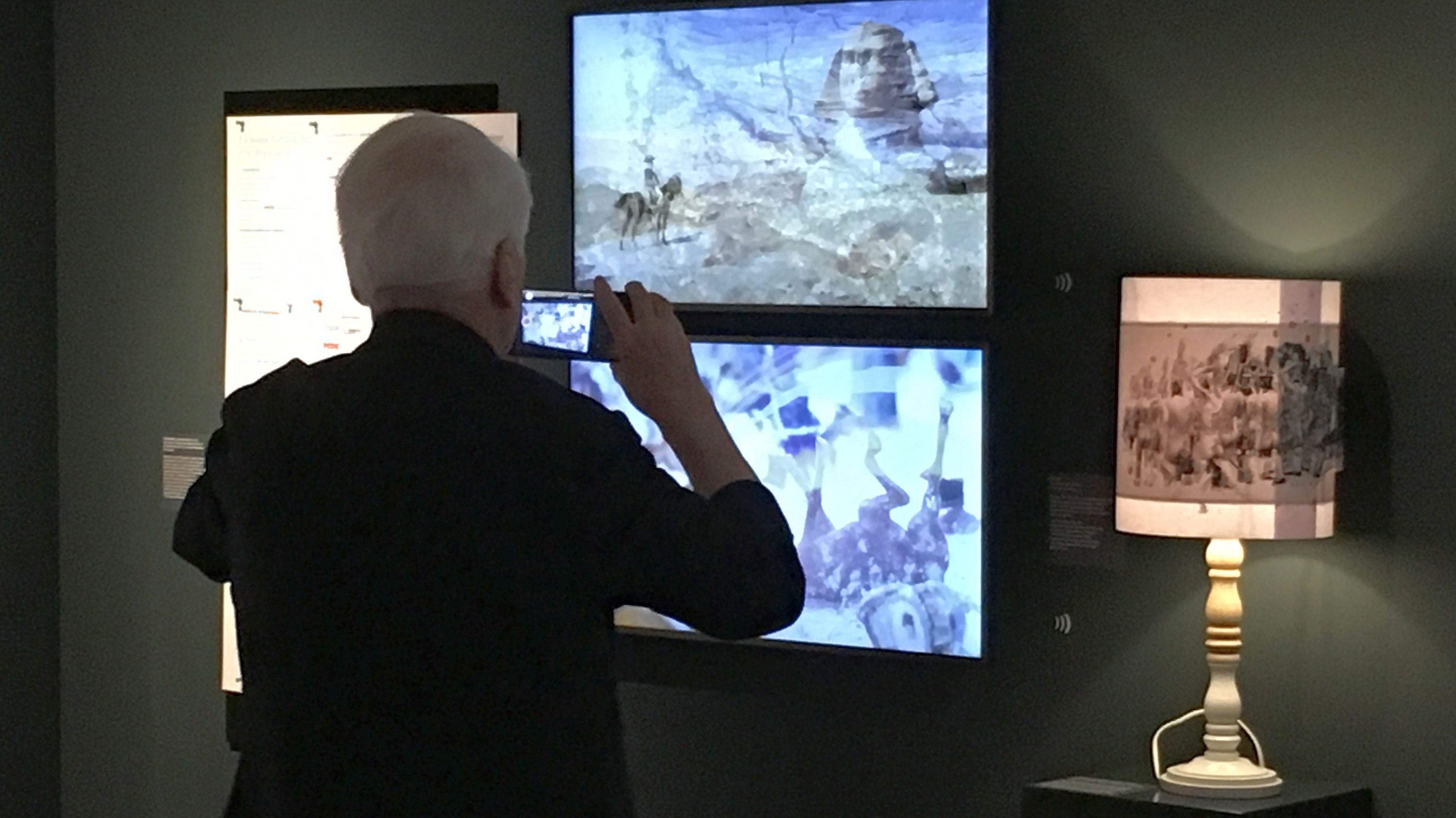Alexander Kluge fotografiert Monitore und eine Lampe seine Ausstellungsinstallation