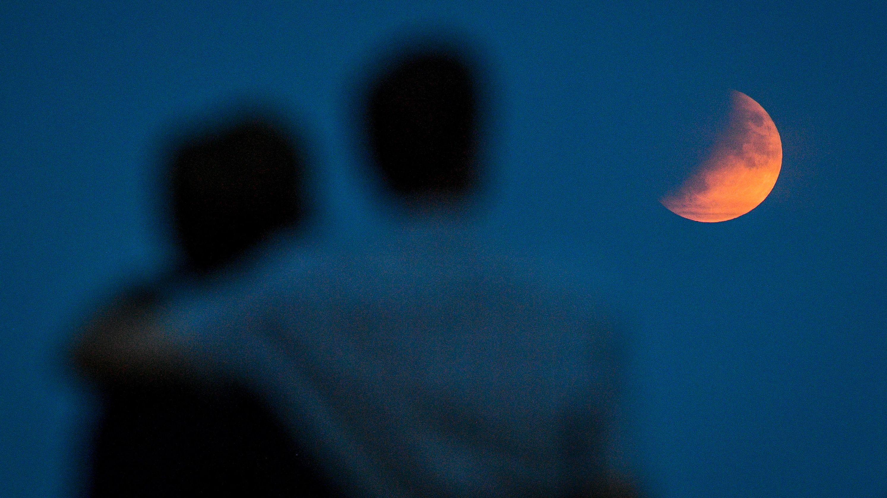 Großbritannien, Sidmouth: EinPaar beobachtet eine partielle Mondfinsternis.