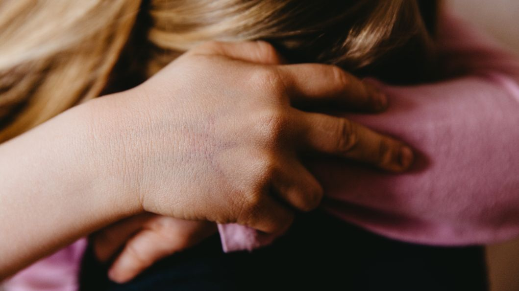 Ein Kind sitzt zusammengesunken und weint (Symbolfoto)