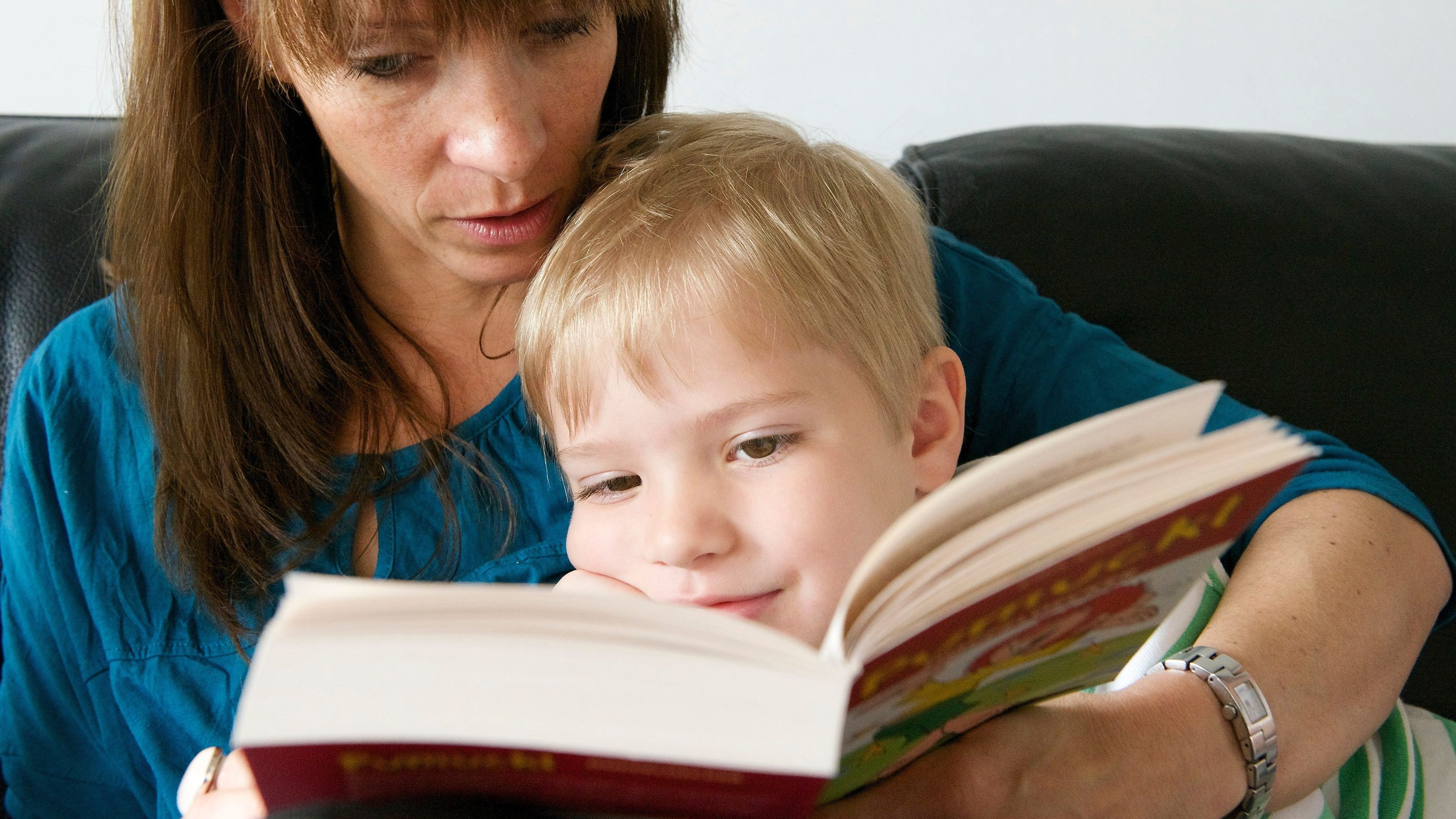 Eine Mutter liest ihrem kleinen Sohn aus einem Kinderbuch vor.