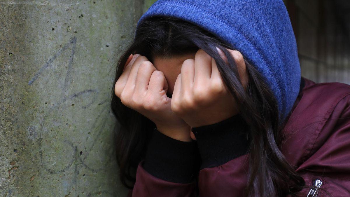 Junge Frau verdeckt ihr Gesicht mit den Händen