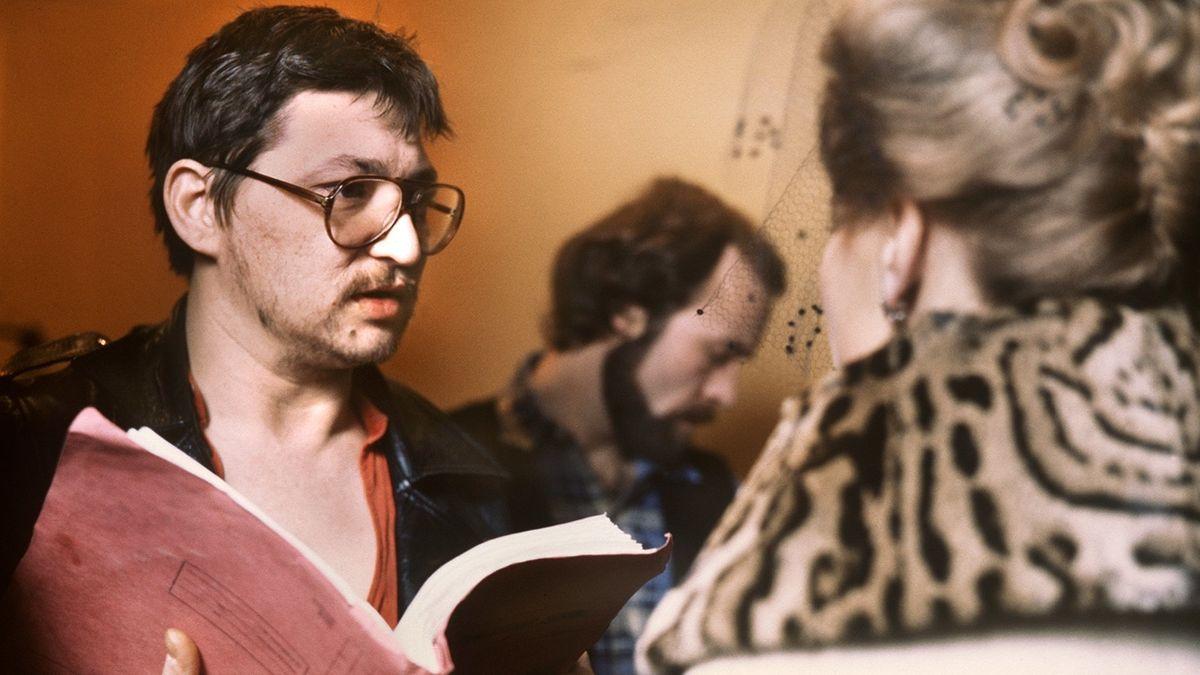 Bei der Arbeit am Set: Rainer Werner Fassbinder hält ein aufgeklapptes rotes Drehbuch in der Hand und spricht mit einer nur von hinten zu sehenden Schauspielerin im Pelz