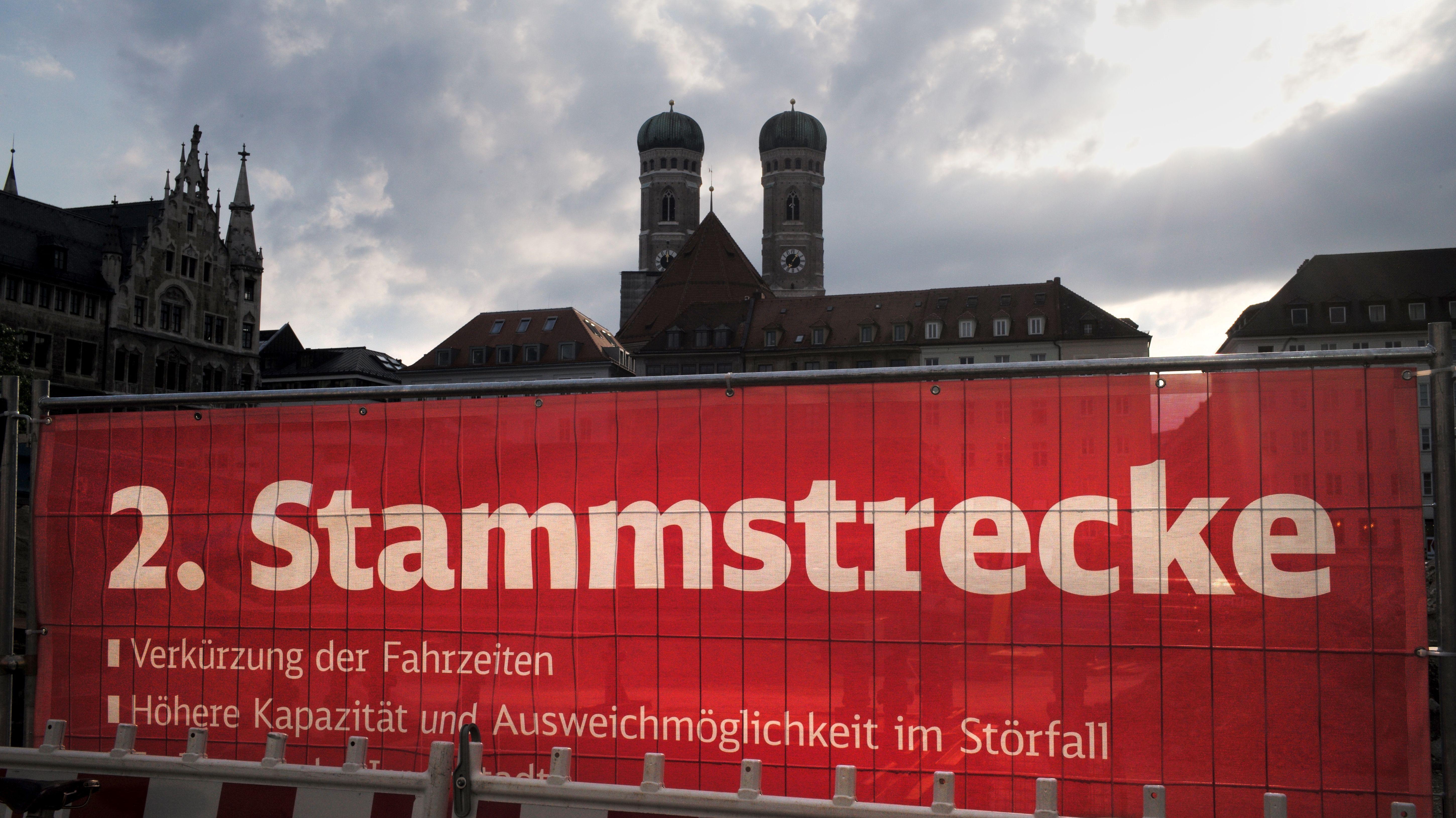"""Der rote Sichtschutz einer Baustelle mit der Aufschrift """"2. Stammstrecke"""" in München"""
