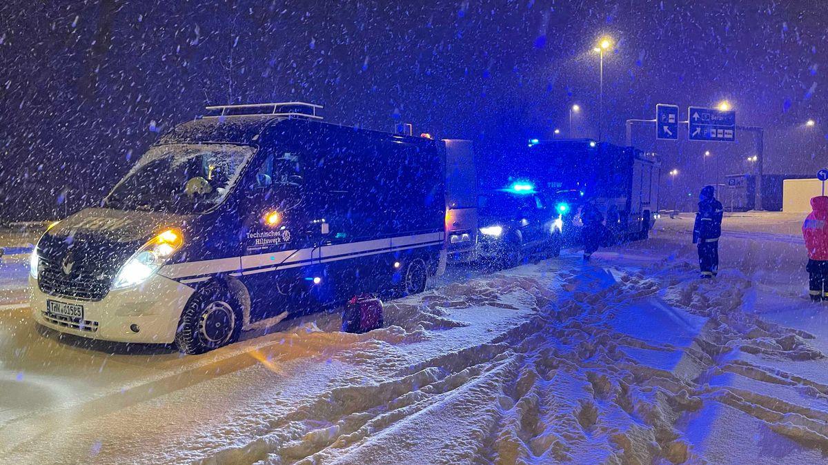Fahrzeuge des THW im Schneetreiben auf der Autobahn.