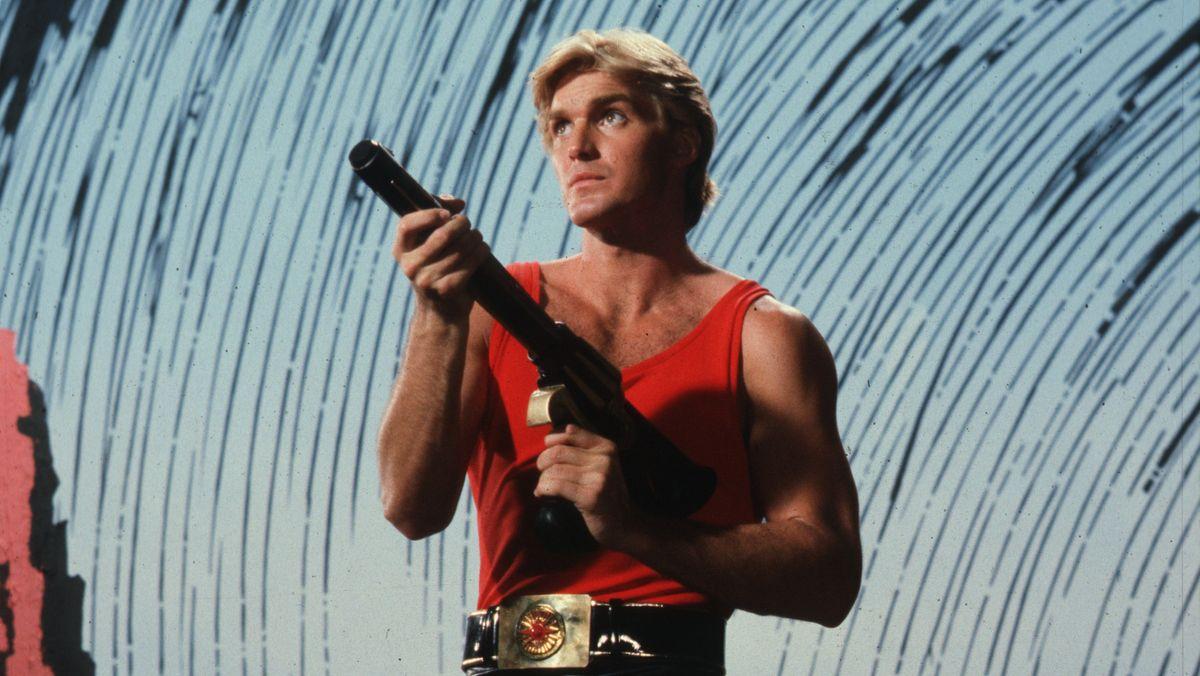 """Ein Mann in rotem Heldenoutfit mit Waffe in der Hand: Szene aus """"Flash Gordon 4k Remastered"""""""