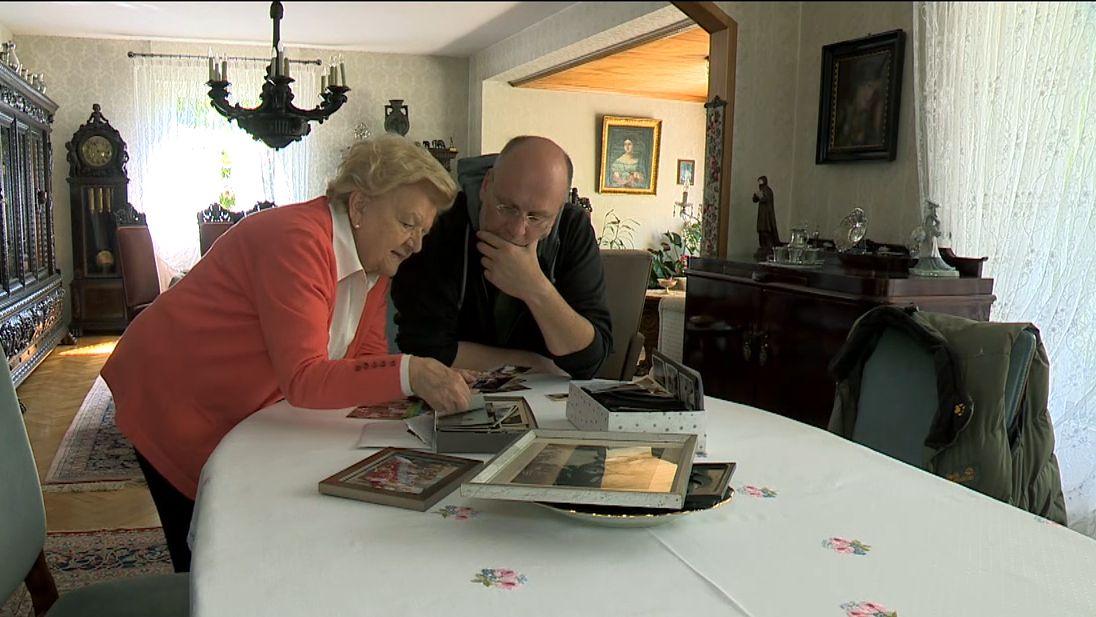 Markus Feulner und seine 96-jährigen Oma stehen an einem Tisch und schauen alte Fotos an.