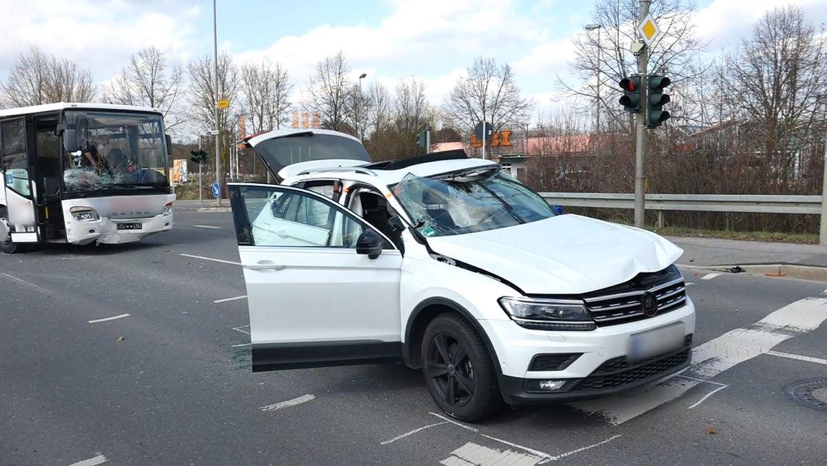 Die beiden Unfallfahrzeuge, ein weißer Pkw und ein weißer Bus stehen auf einer Straße.
