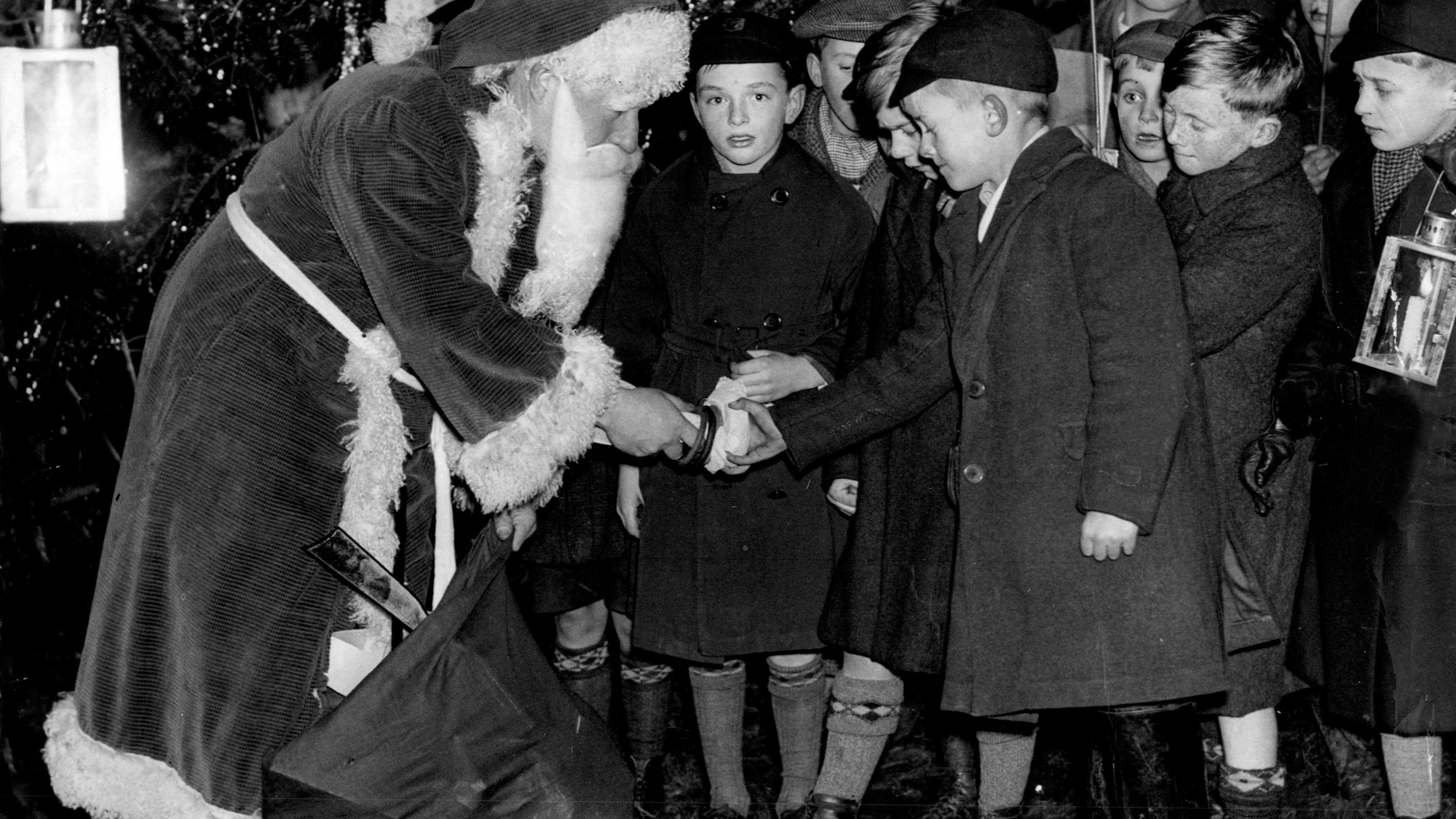 Schwarz-weiß Aufnahme eines Weihnachtsmanns, der Kindern Geschenke gibt in Hunworth, Großbritannien, 1935