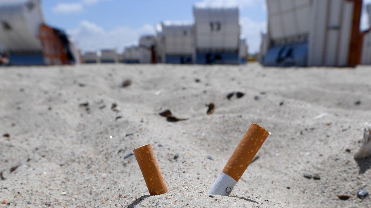 Zigarettenkippen stecken im Sand eines Strandes bei Travemünde.