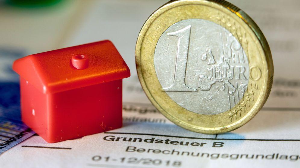 Eine Euro-Geldmünze sowie ein Spielzeughaus stehen auf einem Abgabenbescheid für die Entrichtung der Grundsteuer | Bild:picture alliance/Jens Büttner/ZB/dpa