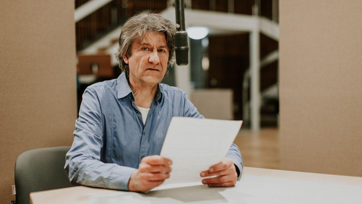 Ein Mann sitzt mit einem Blatt Papier in der Hand vor einem Mikrofon