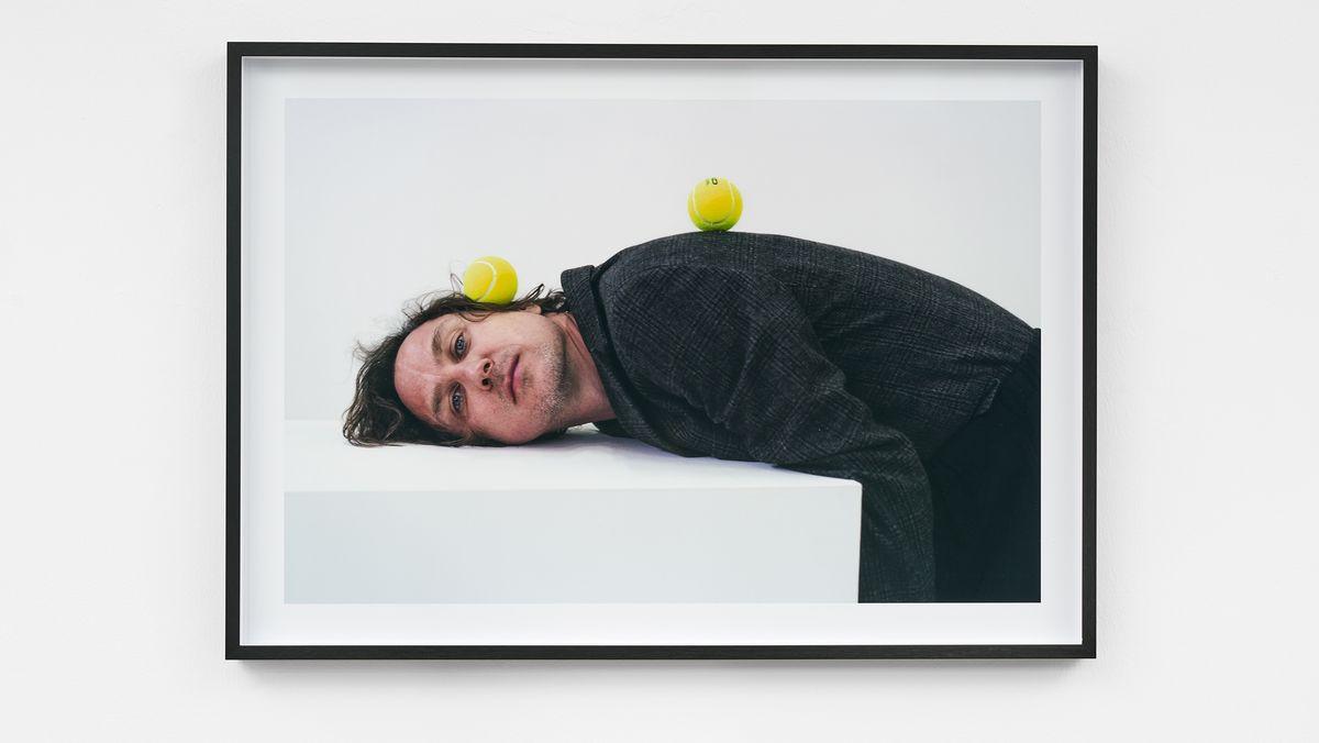 Lars Eidinger lehnt mit dem Kopf und dem Oberkörper auf einer Tischplatte und blickt müde die Betrachter an, während er zwei Tennisbälle auf seinem Körper im Stillstand zu halten versucht.