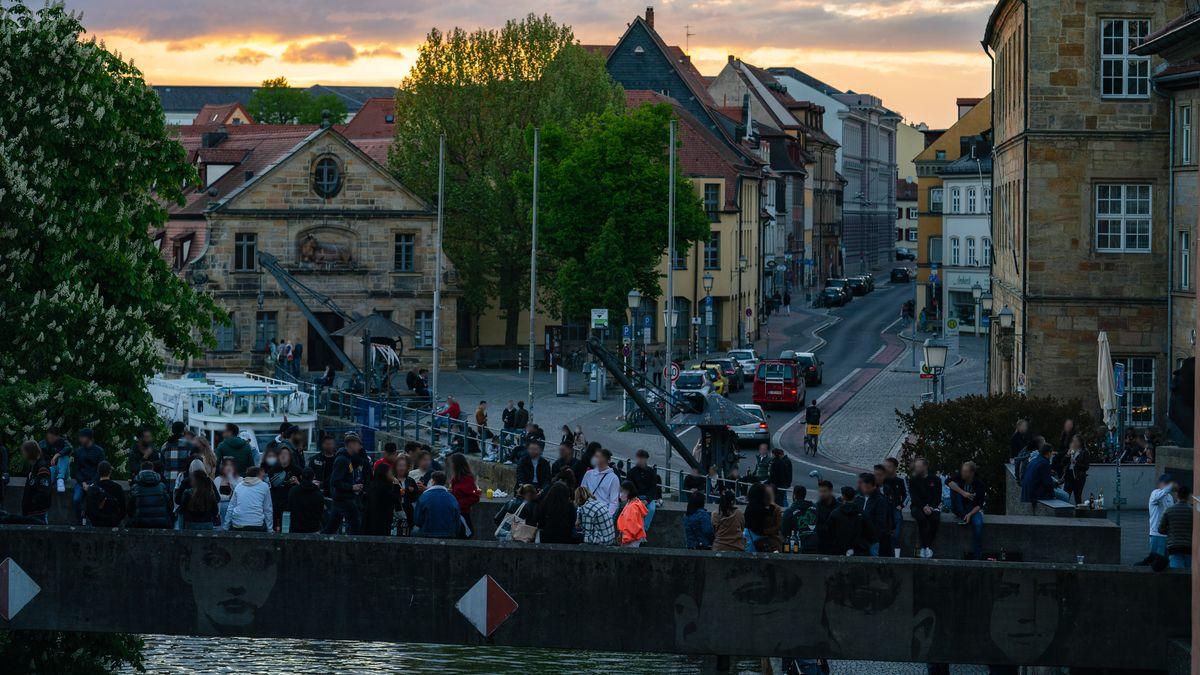 Zahlreiche Menschen stehen bei später Abenddämmerung auf der Unteren Brücke beim alten Rathaus.