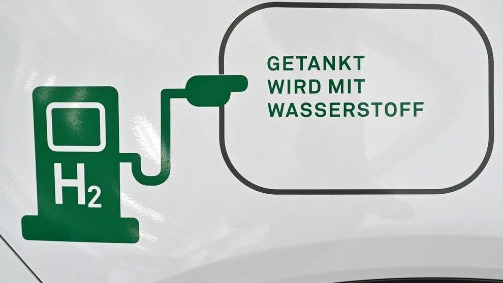"""Eine grüne Tankstelle mit der Aufschrift """"H2"""" und der Sprechblase """"Getankt wird mit Wassersatoff""""."""