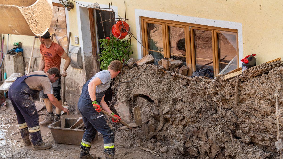 Anwohner graben ein Haus aus, das von Schlamm- und Geröllmassen bis zu drei Meter hoch eingeschlossen ist