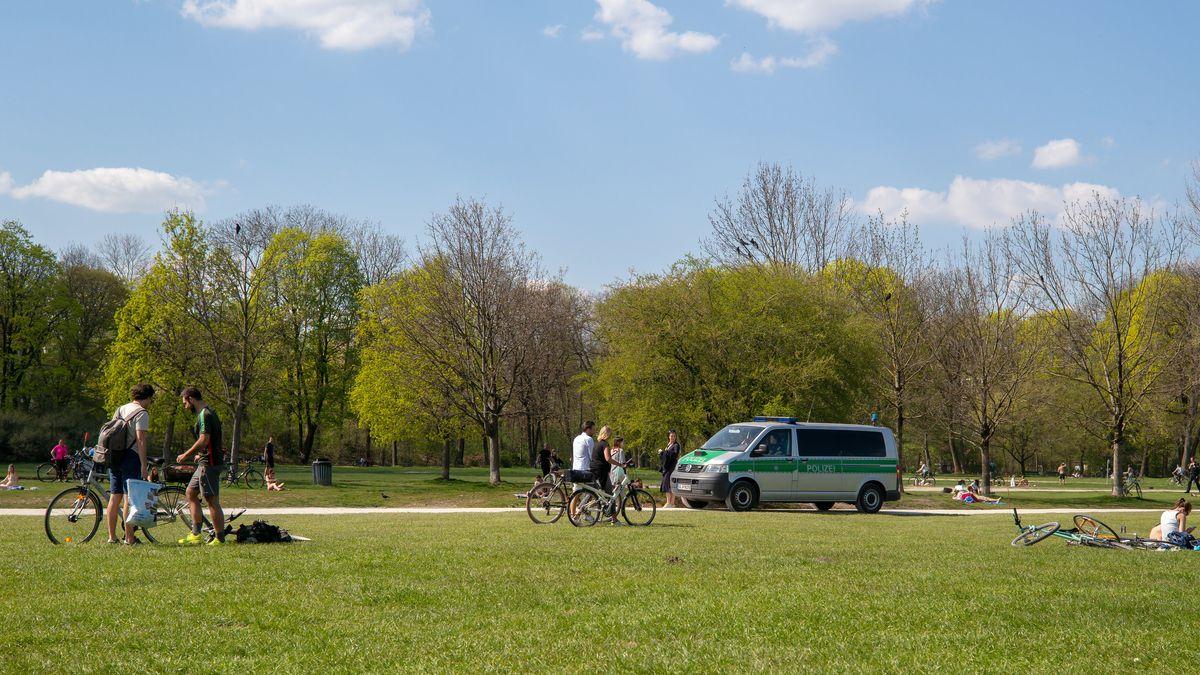 Ein Polizeiauto und einige Passanten im Englischen Garten in München