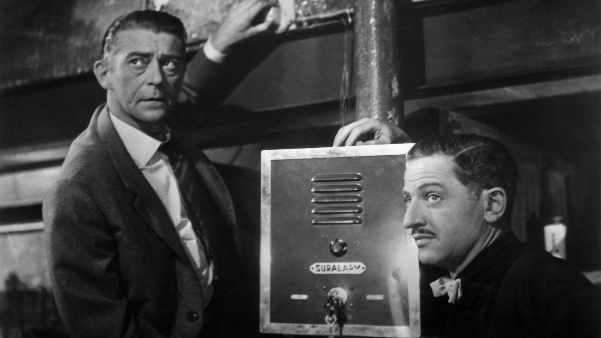 """Filmszene aus """"Rififi"""": Zwei Männer in einem Kellergang an einer Alarmanlage (schwarzweiß, 50er-Jahre)"""