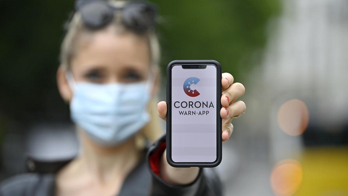 Eine Frau zeigt die Corona-Warn-App auf ihrem Smartphone vor