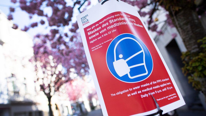 Bonn: Auf das Tragen einer Maske weißt ein Schild vor den blühenden Kirschbäumen in der Heerstraße hin.