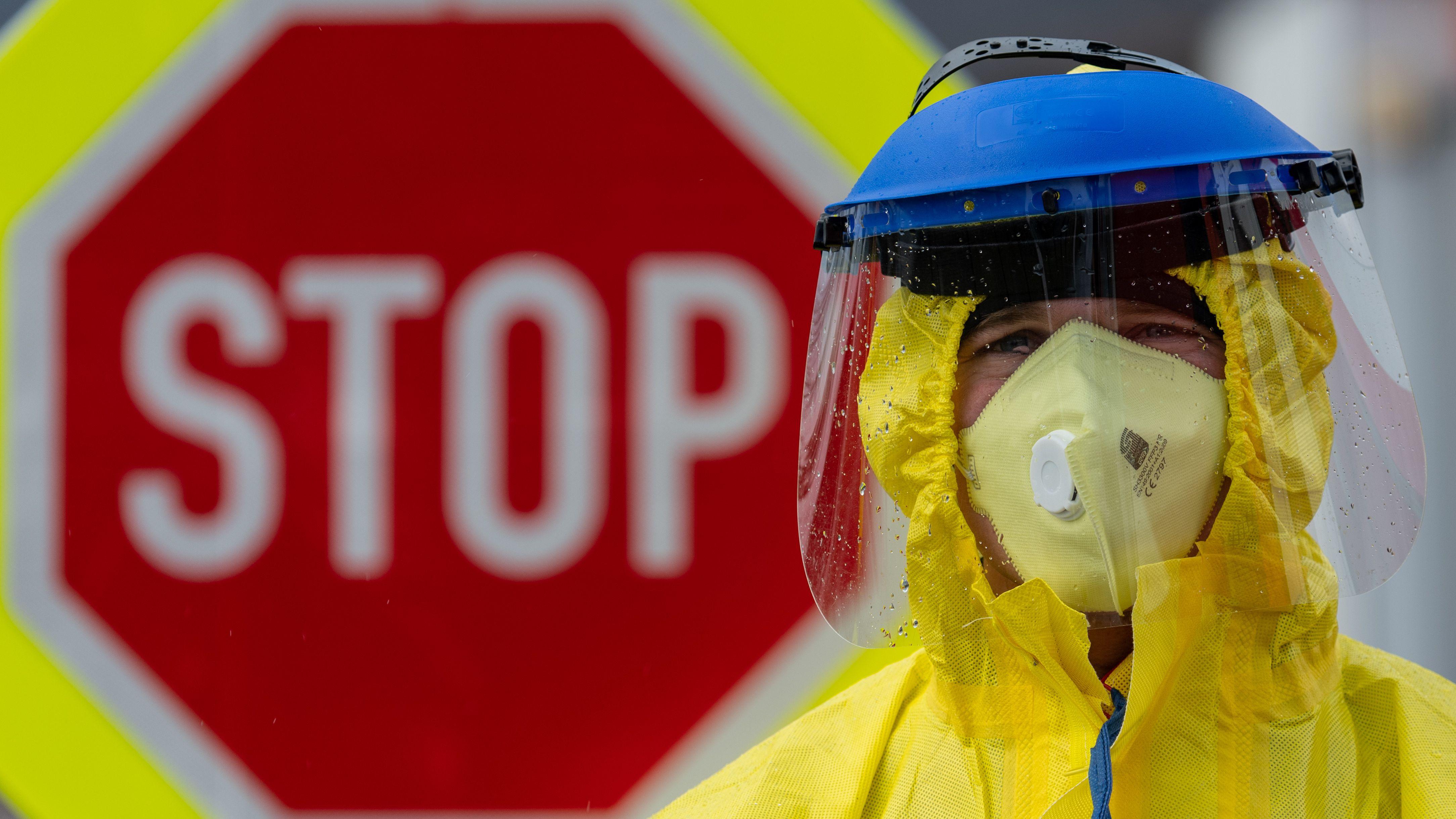 An der tschechischen Grenze steht ein Feuerwehrmann mit Schutzbekleidung vor einem Stopp-Schild