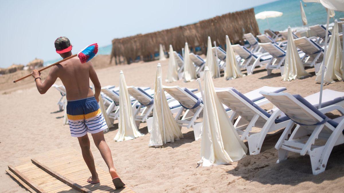 Türkei, Antalya: Ein Mann mit einem Besen geht an einem leeren Strand in Antalya entlang.