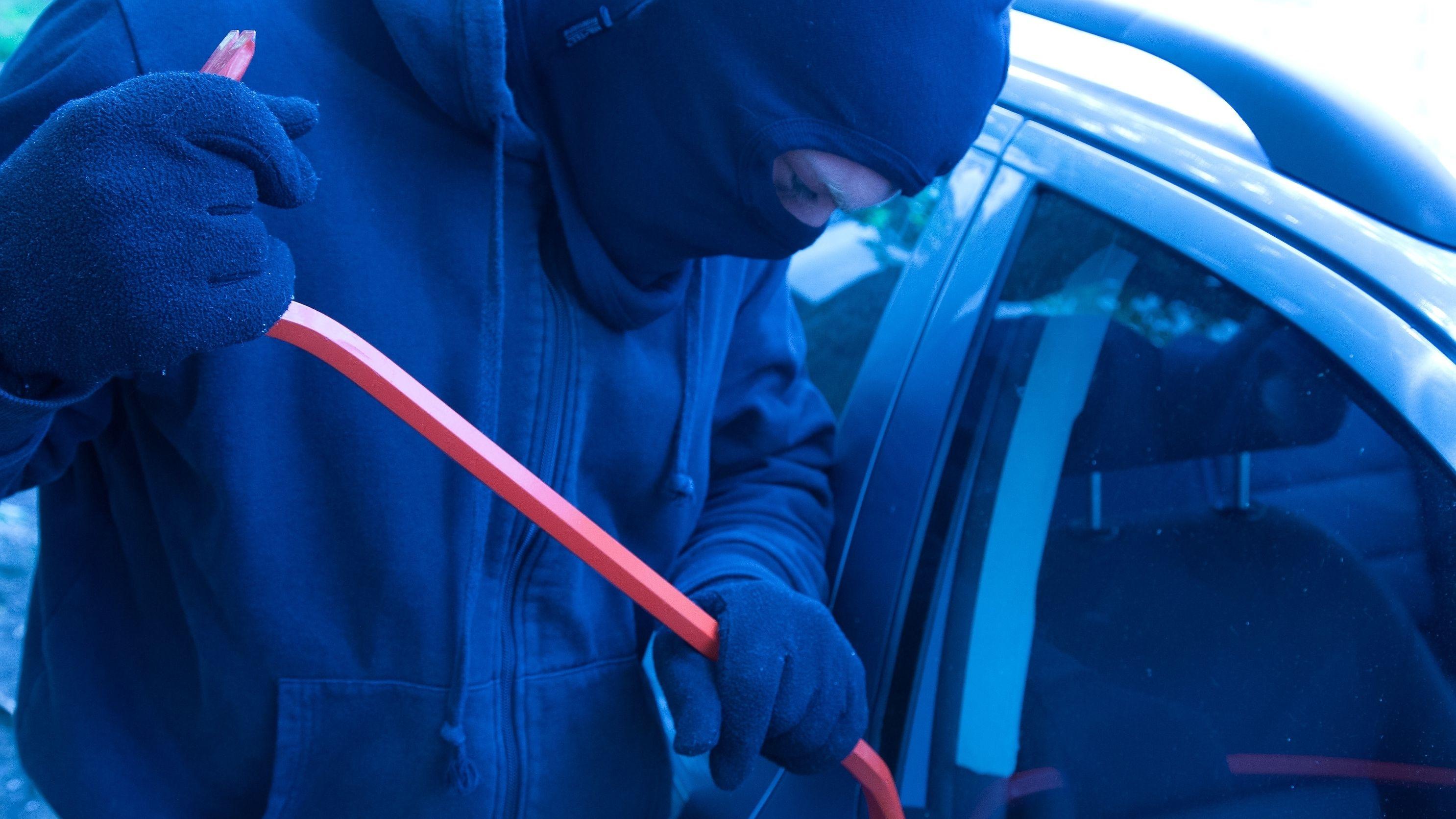 Ein vermummter Mann versucht mit einem Brecheisen ein Auto aufzubrechen.
