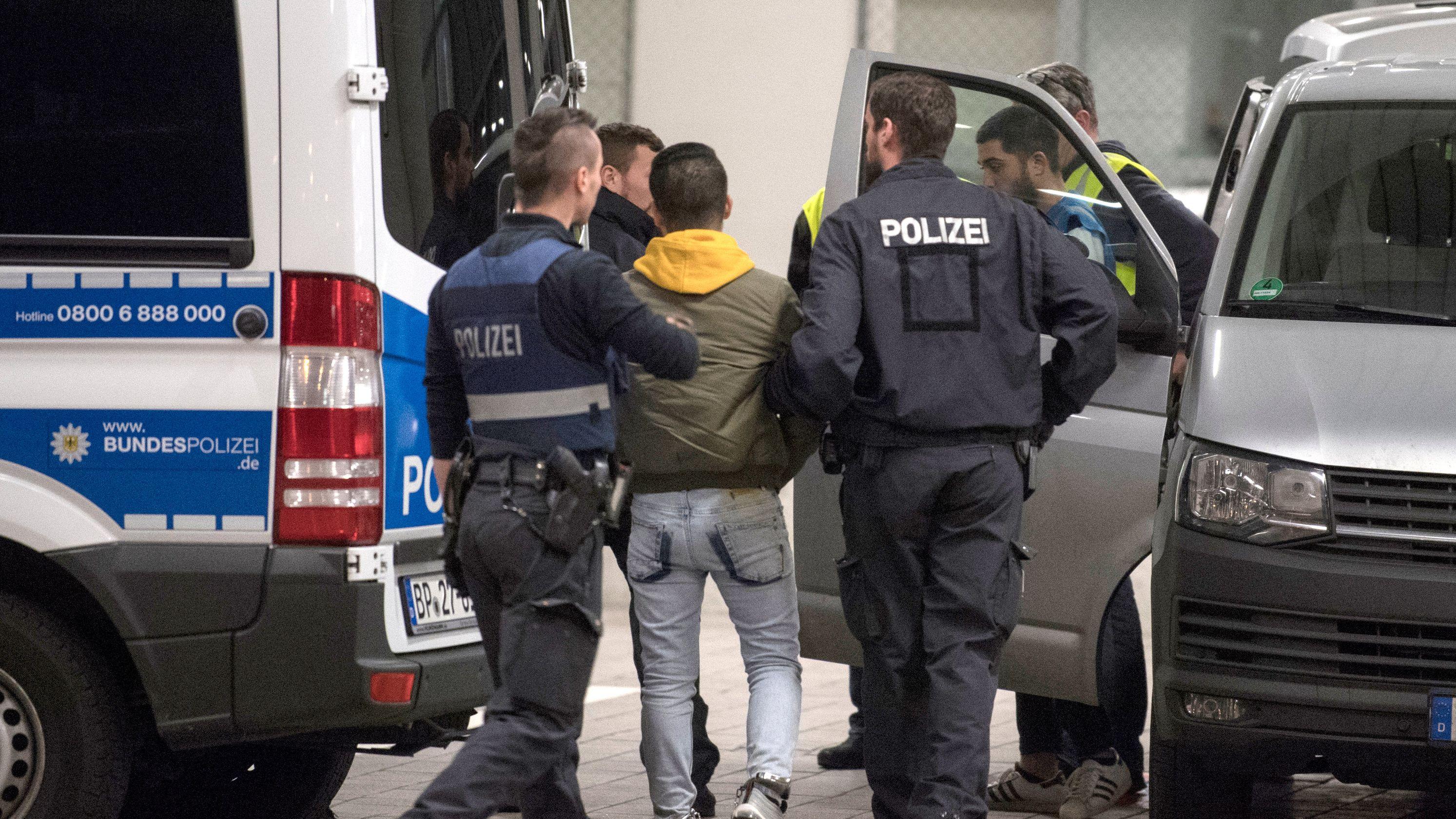 Ein junger Mann wird in Hessen von Polizisten zur Abschiebung zum Flughafen gebracht, Archivbild von 2018.