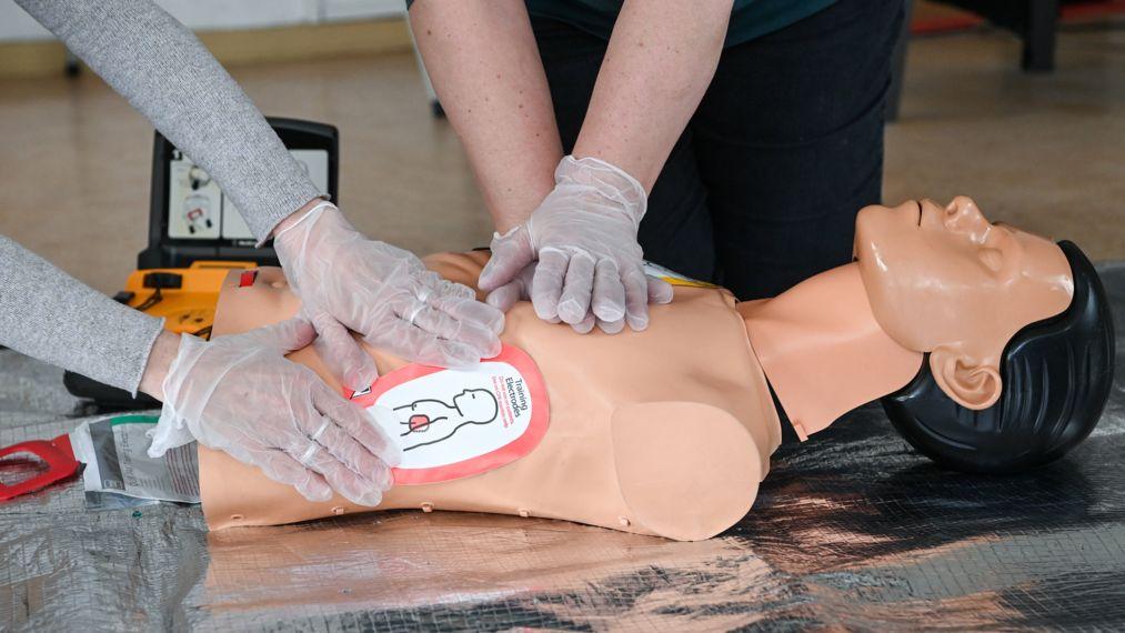 Die Hände zweier Menschen in Handschuhen üben Herzdruckmassage an einer Übungspuppe für Erste Hilfe.