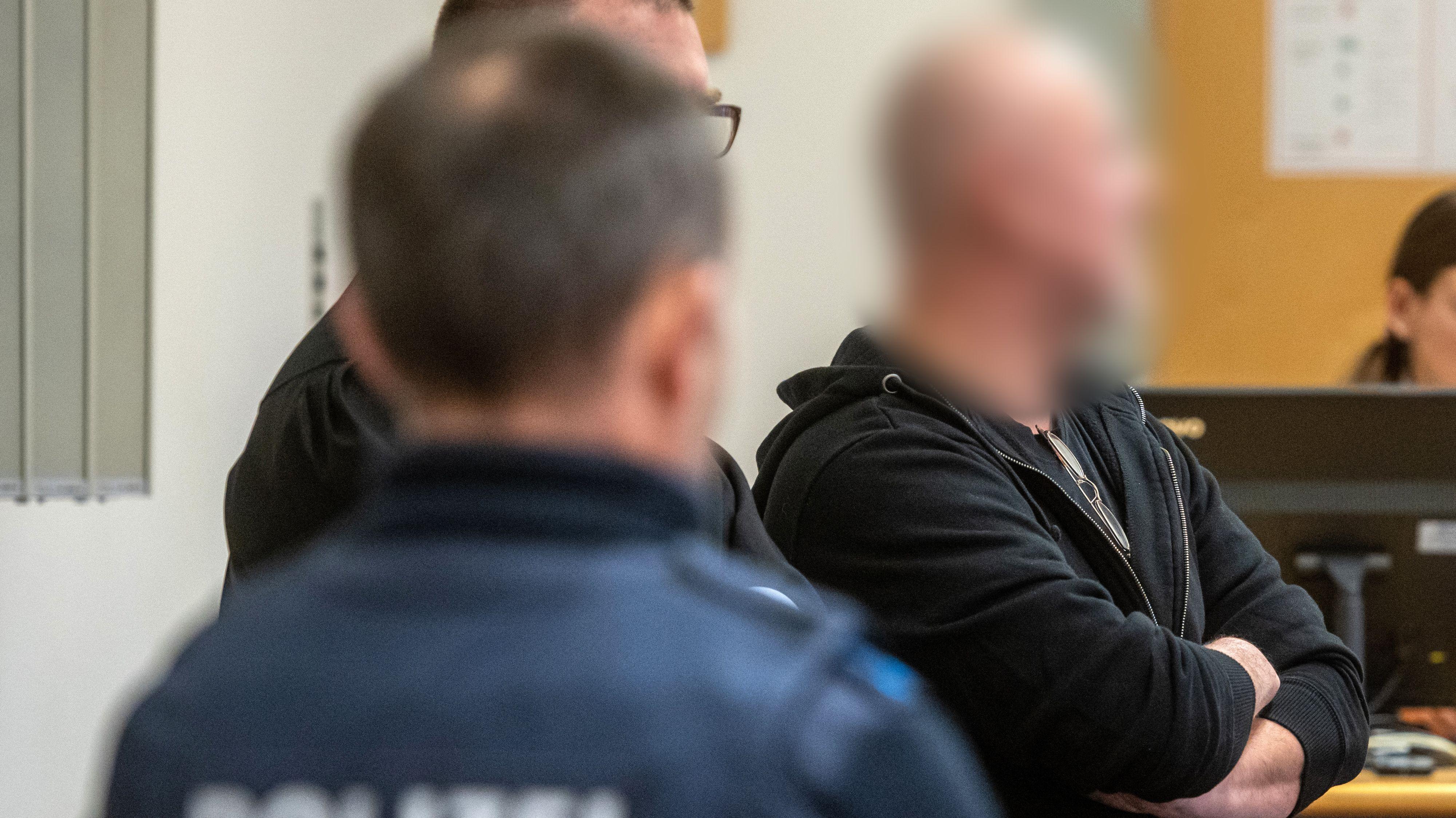 Der Angeklagte (re.) steht im Verhandlungssaal des Landgerichts neben seinem Verteidiger Sebastian Gaßmann (M) und einem Polizisten.