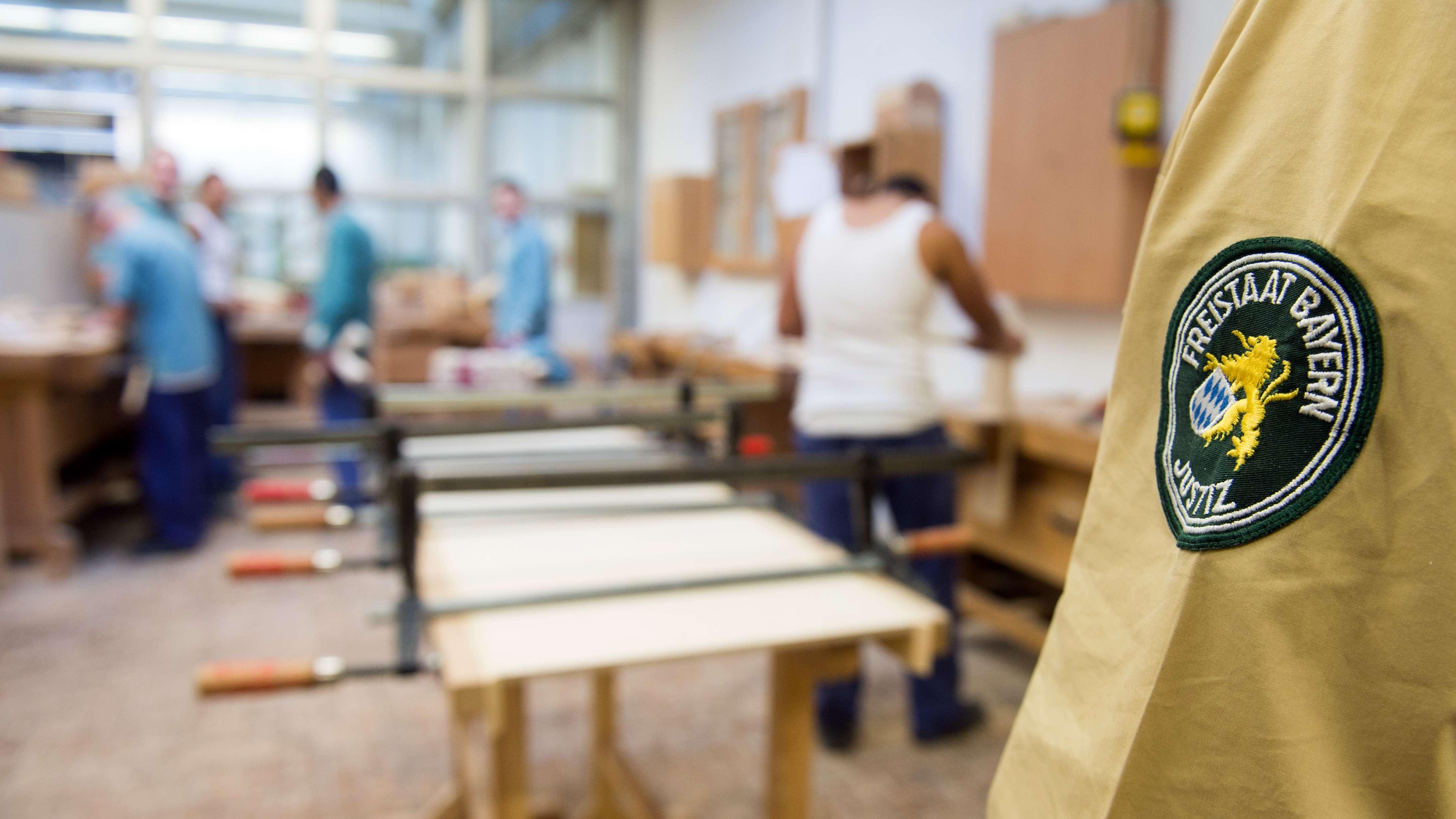 Häftlinge arbeiten in der Jugendhaftanstalt Neuburg-Herrenwörth in einer Schreinerei und werden dabei von einem Justizbeamten beaufsichtigt.