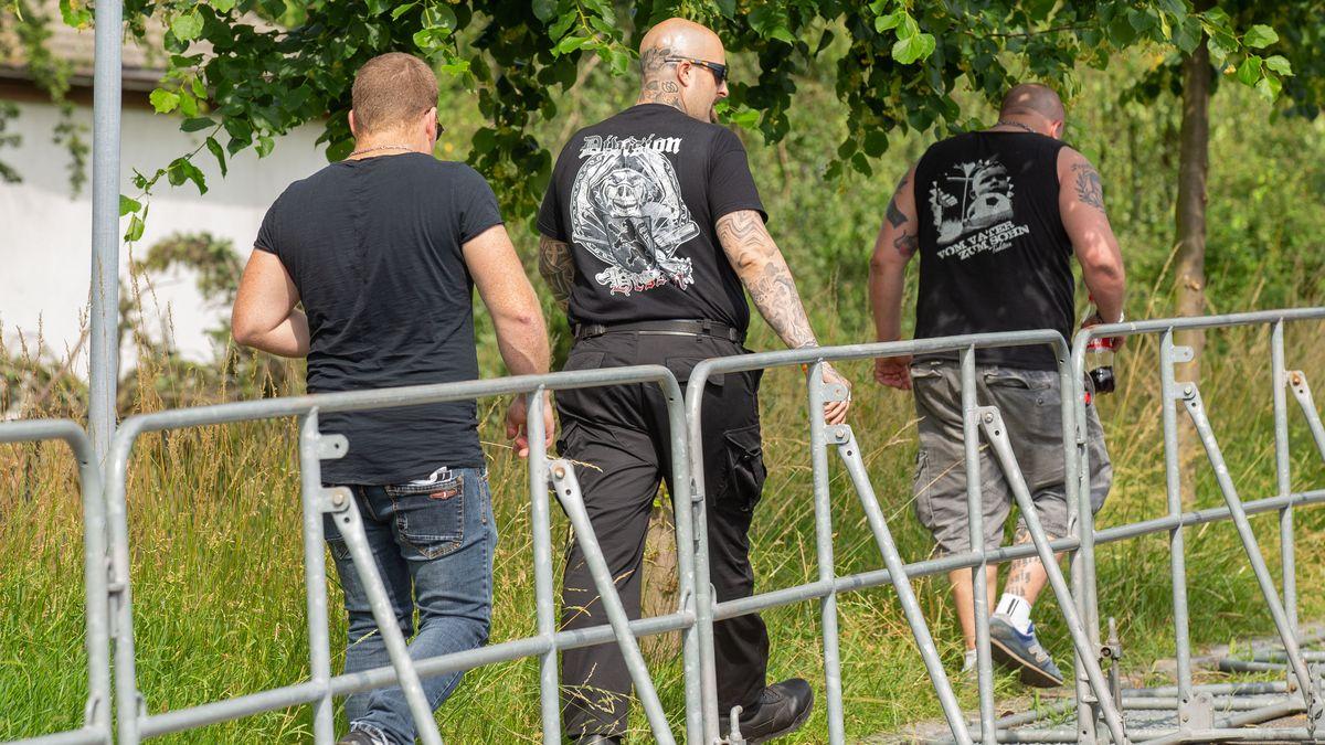 Drei Männer in schwarzen T-Shirts hinter einer Absperrung