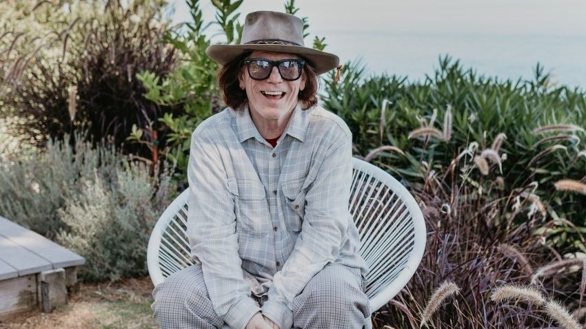 Leadsänger Bob Forrest mit Brille und Cowboyhut in einem Strandstuhl, im Hintergrund Blick aufs Meer
