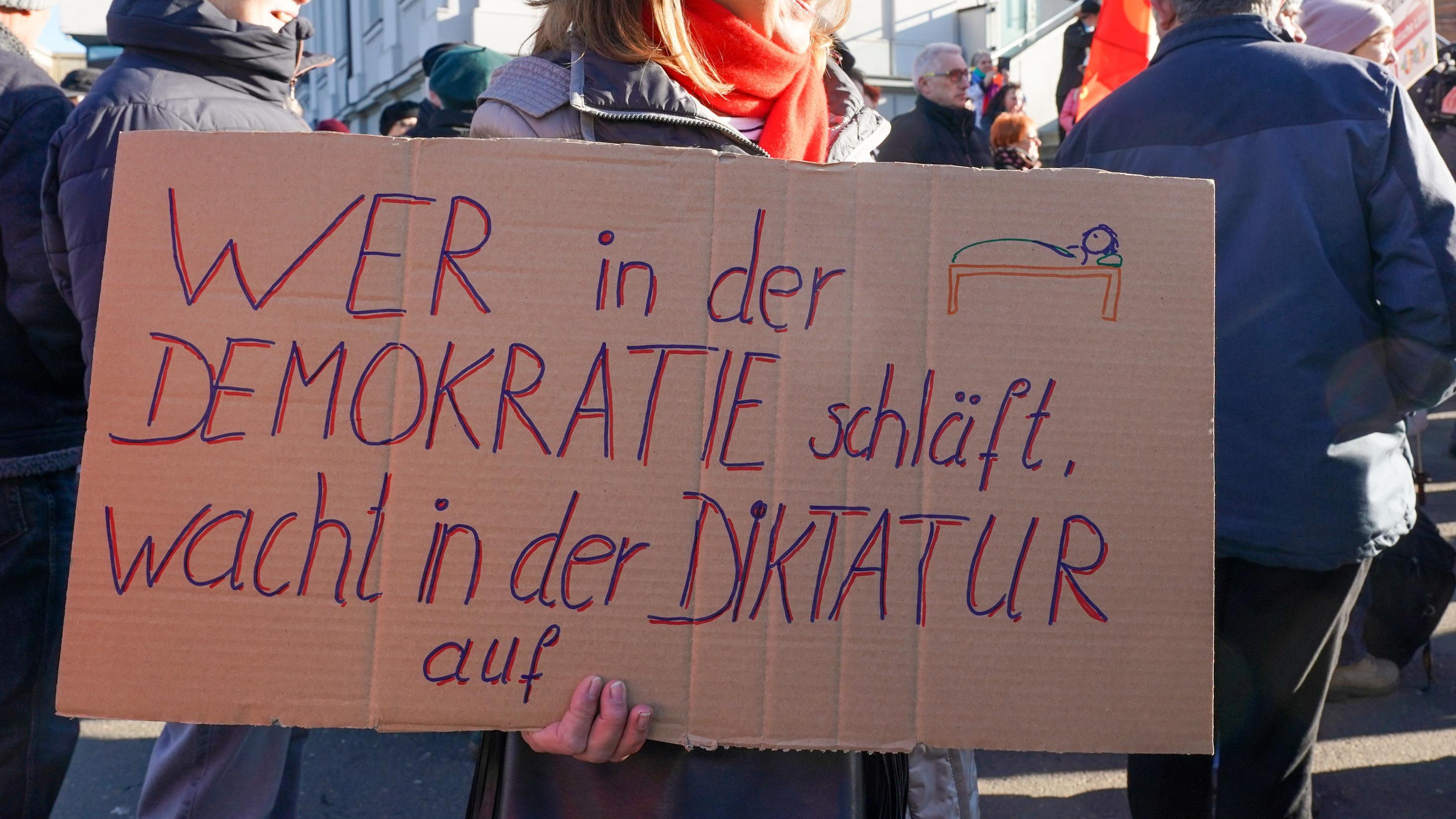 Eine Demonstrantin hält ein Plakat mit der Aufschrift «wer in der Demokratie schläft, wacht in derr Diktatur auf» während einer Kundgebung und Demonstration unter dem Motto «Für ein weltoffenes Thüringen - Gegen faschistische Paktierereien».