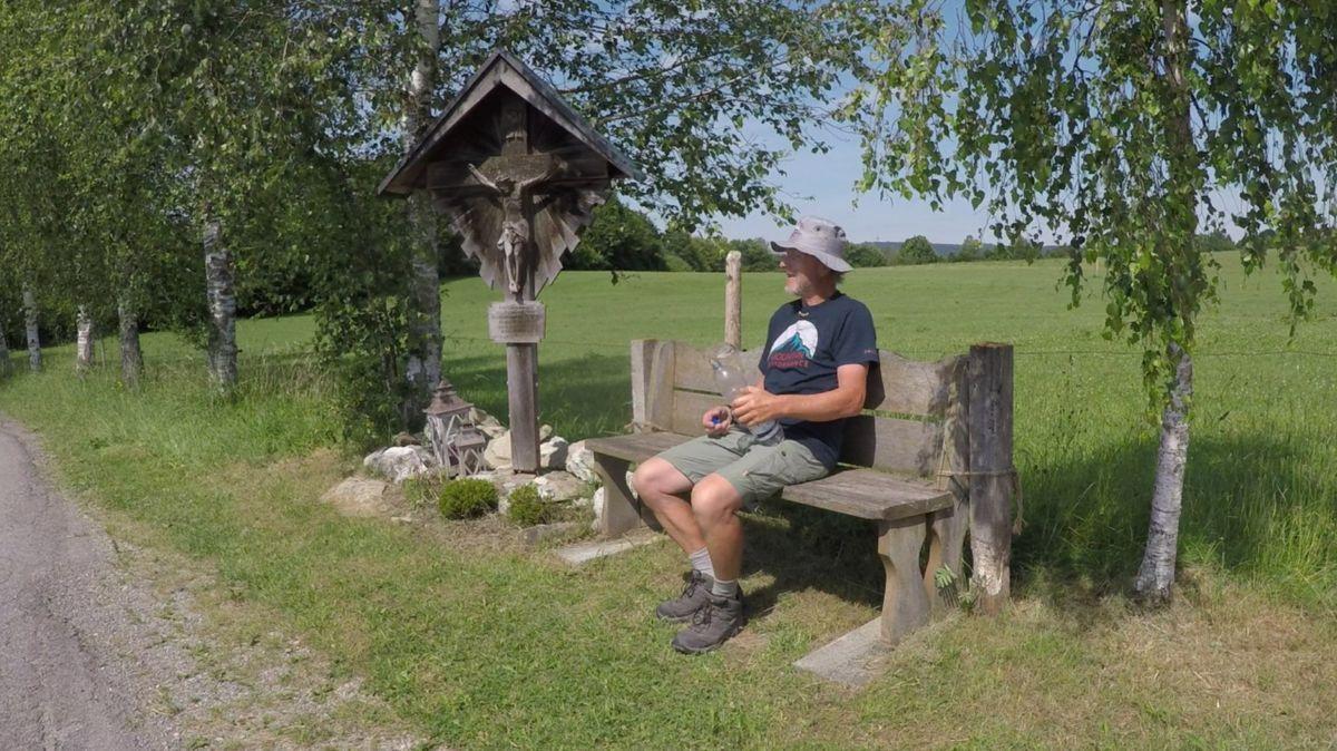 Walter Wärthl sitzt mit Hut und Wasserflasche auf einer Bank am Wegesrand.