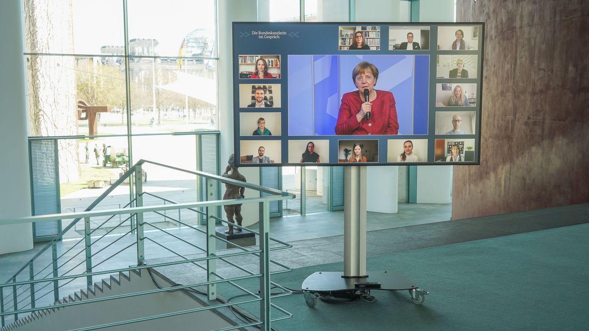 Bildschirm mit Teilnehmern im Treppenhaus des Kanzleramts