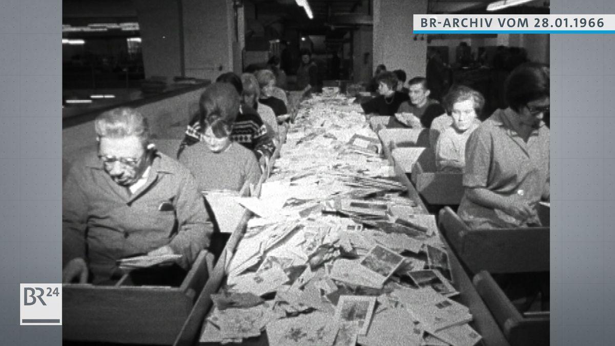 Post-Mitarbeiter am Fließband beim Sortieren von Briefen und Postkarten.
