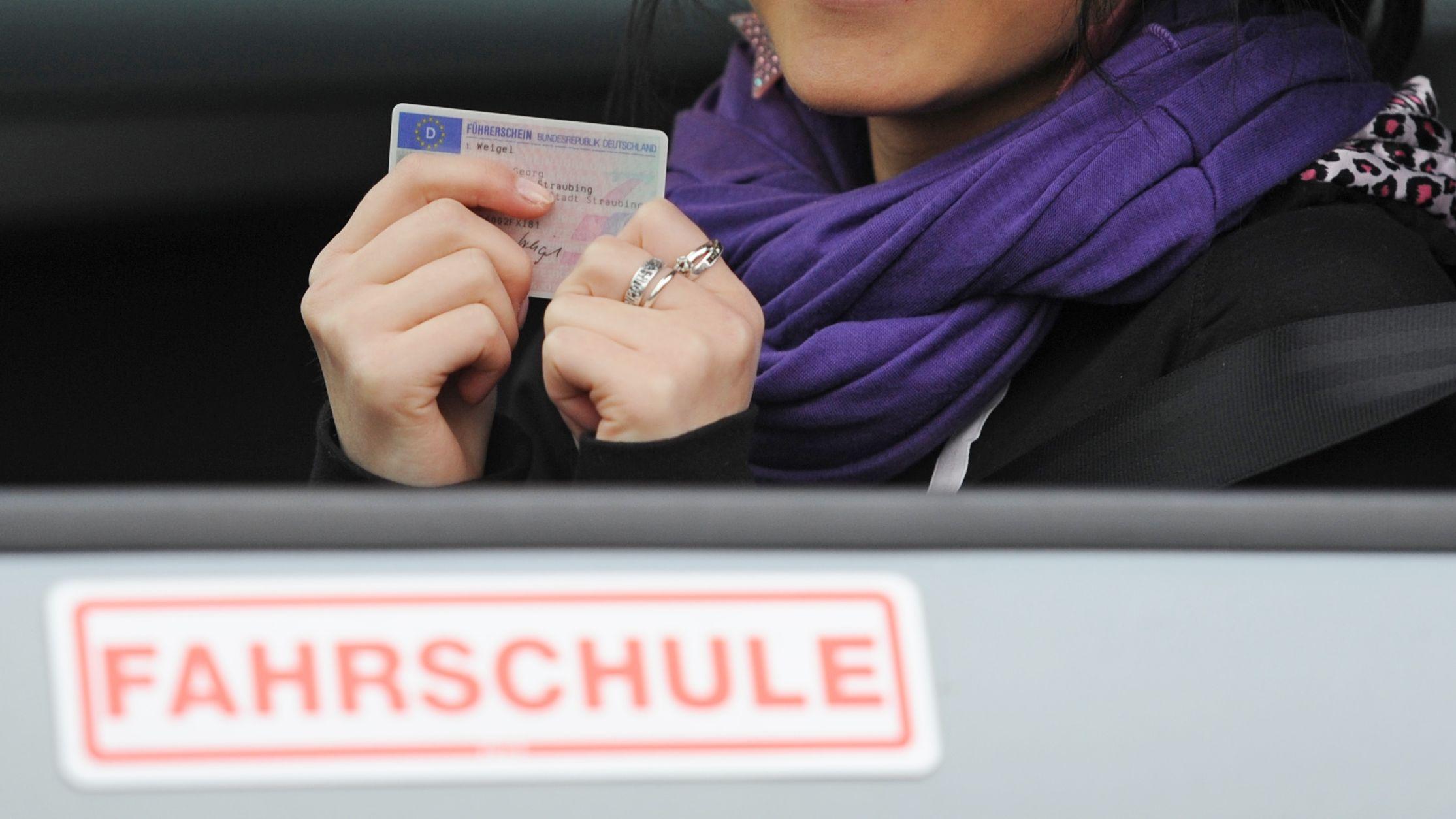 Eine junge Frau sitzt in einem Fahrschulauto und hält den Führerschein in den Händen