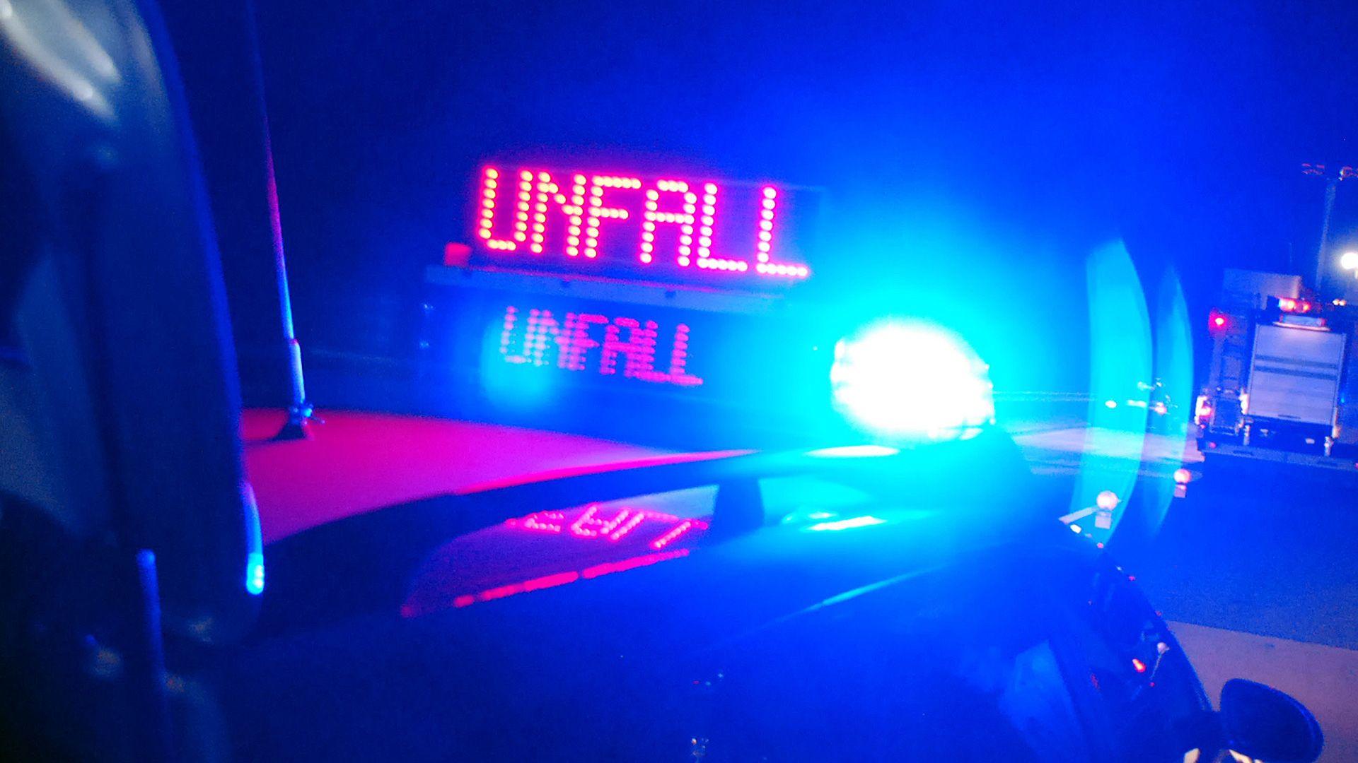 Polizeiauto mit blinkender Unfall-Anzeige und Blaulicht