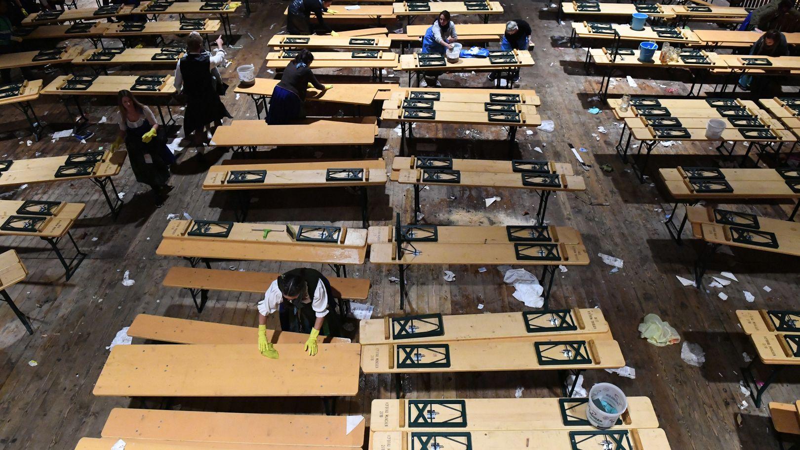 Bedienungen räumen im Hofbräu-Zelt nach dem traditionellen Kehraus Tische zusammen.