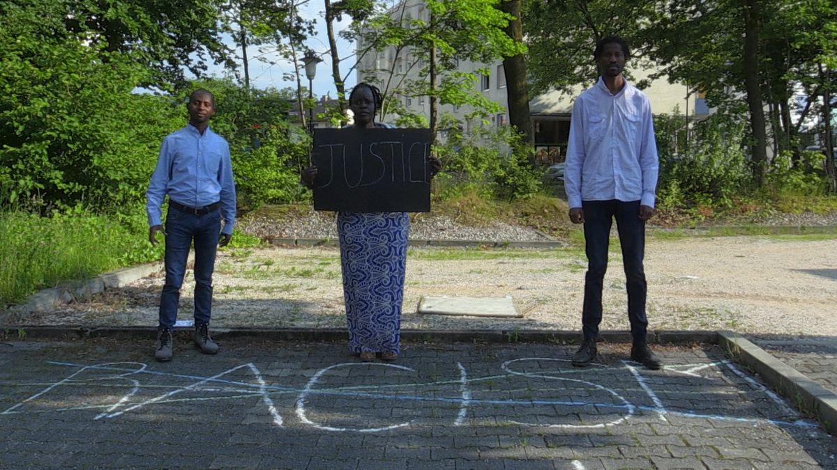 Drei Bewohner des Ankerzentrums Waldkraiburgs, die Frau trägt ein Schild mit der Aufschrift Justice