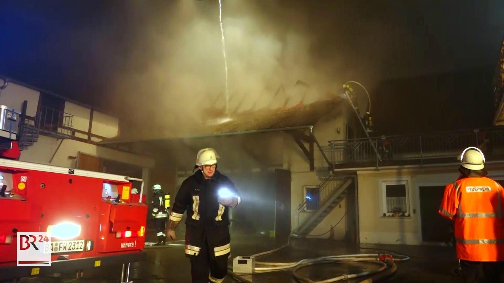Scheunenbrand in Ampferbach bei Burgebrach im Landkreis Bamberg. Der Dachstuhl qualmt, die Balken liegen frei. Zwei Feuerwehrmänner sind im Einsatz.