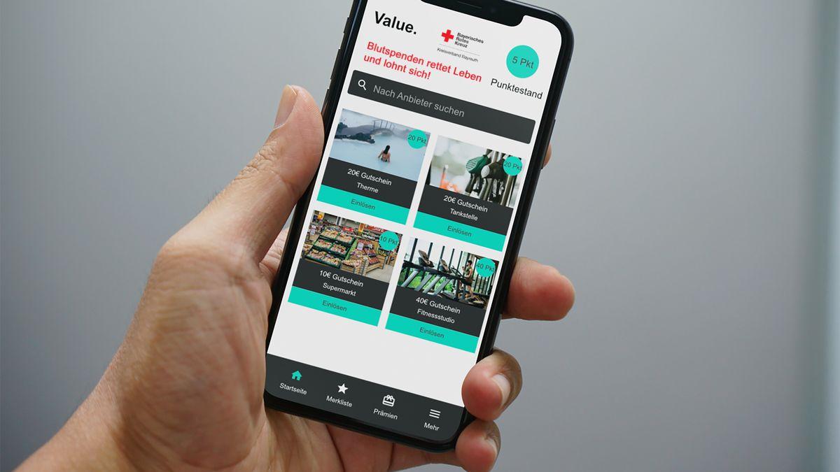 Eine Hand hält ein Smartphone in der Hand, auf der die BRK-App zu sehen ist
