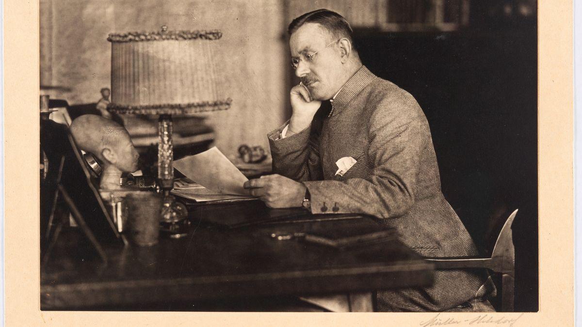 Schwarz-weiß-Bild; Thomas Mann am Schreibtisch, den Kopf nachdenklich in die Hand gestützt und ein Blatt lesend, München, um 1922