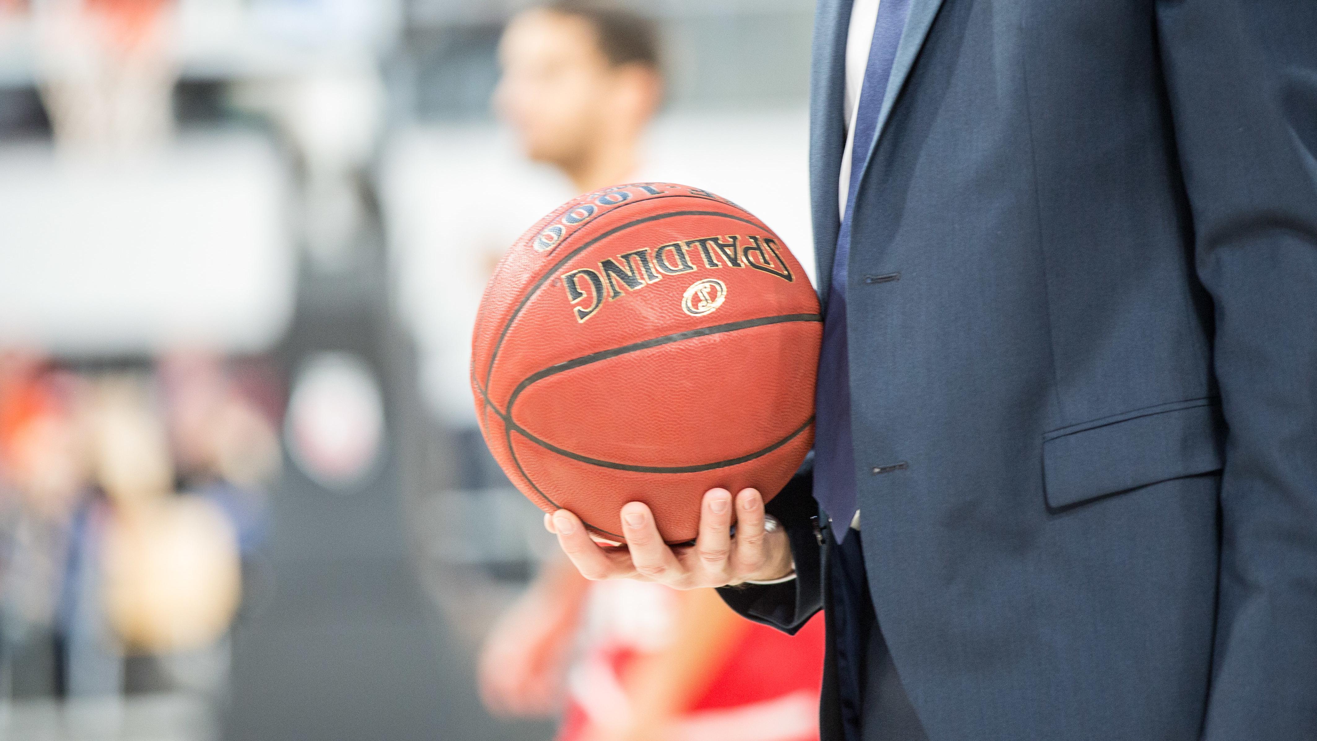 Ein Mann hält einen Basketball.