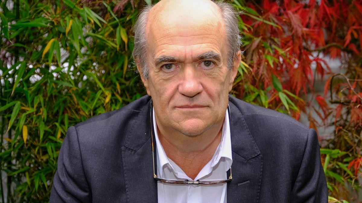 Autor Colm Tóibín blickt, vor herbstbunten Weinranken stehend, in die Kamera