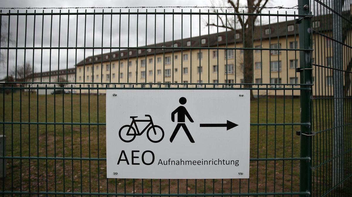 Ein Schild, das am Zaun des Ankerzentrums Bamberg hängt, weist den Weg zur Aufnahmeeinrichtung, dahinter die Unterkünfte für die Flüchtlinge.
