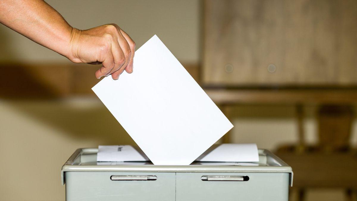 Hand mit Wahlschein an Wahlurne