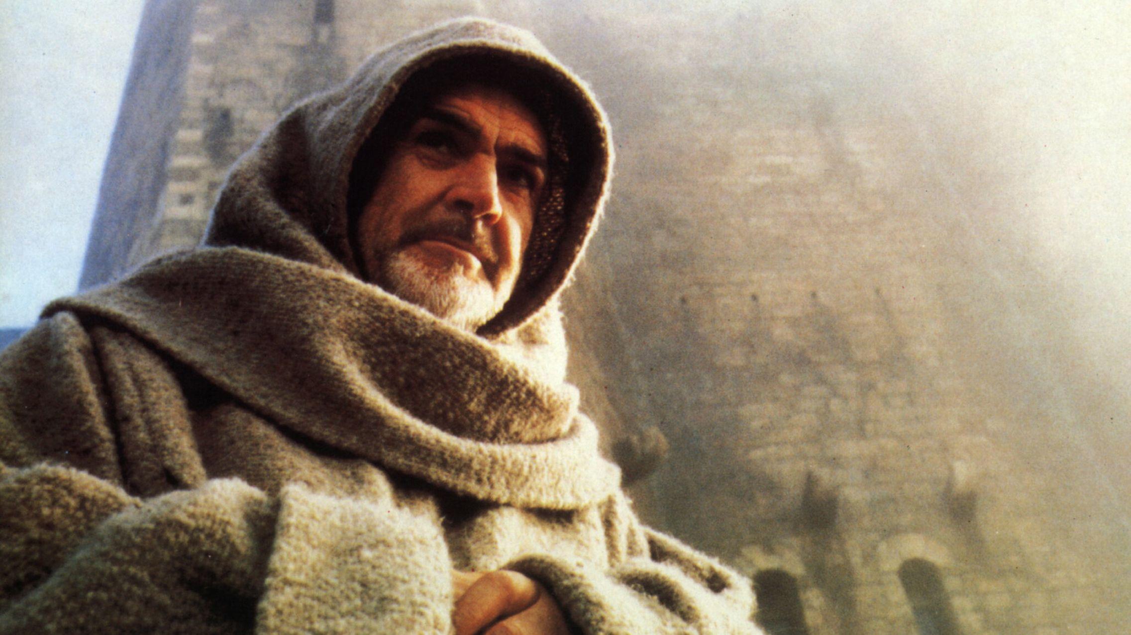 """Schauspieler Sean Connery steht in Mönchskutte und Kapuze vor einem monumentalen Burgbau (Filmbild aus """"Der Name der Rose"""", 1986)"""